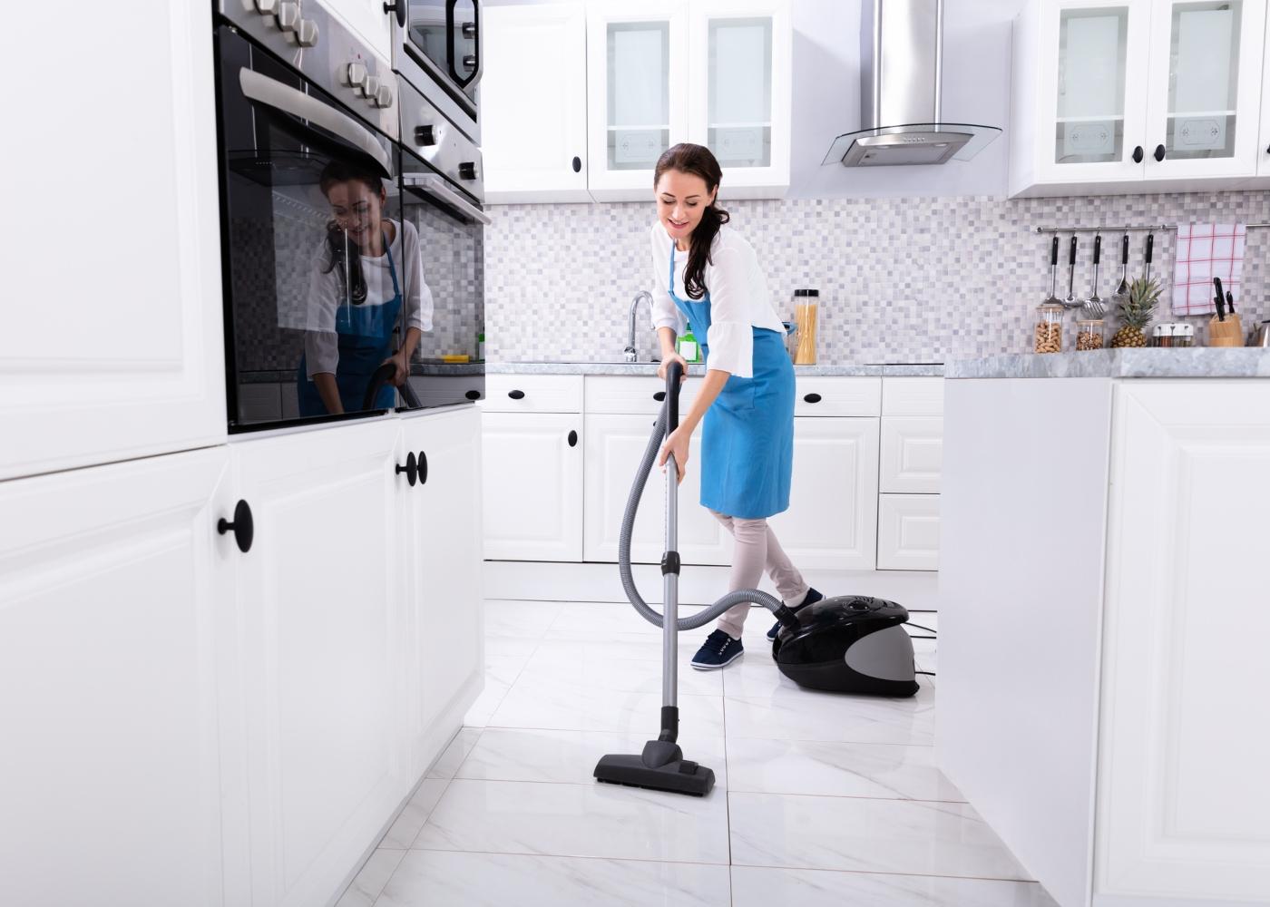 mulher a aspirar uma cozinha