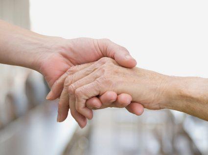 Faltas ao trabalho justificadas para cuidar de familiares: filho a segurar mão do pai idoso
