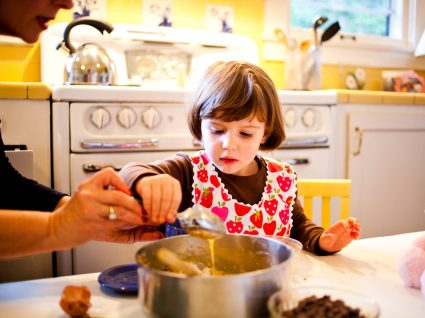 Criança ajuda. amãe a preparar jantar em família