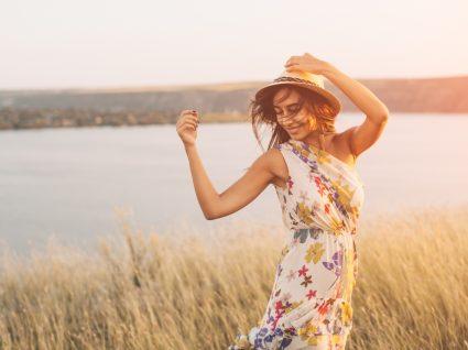 jovem com vestido estampado floral no meio da seara