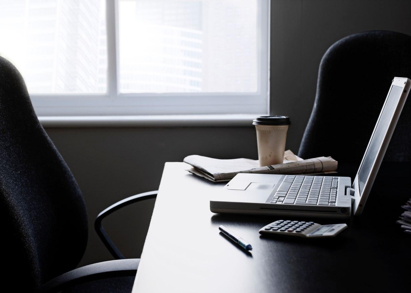 sala de trabalho com computador na mesa mas sem ninguém