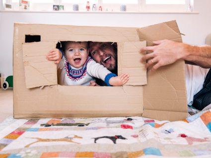 pai e filho bebé a brincar numa casa feita de papel cartão