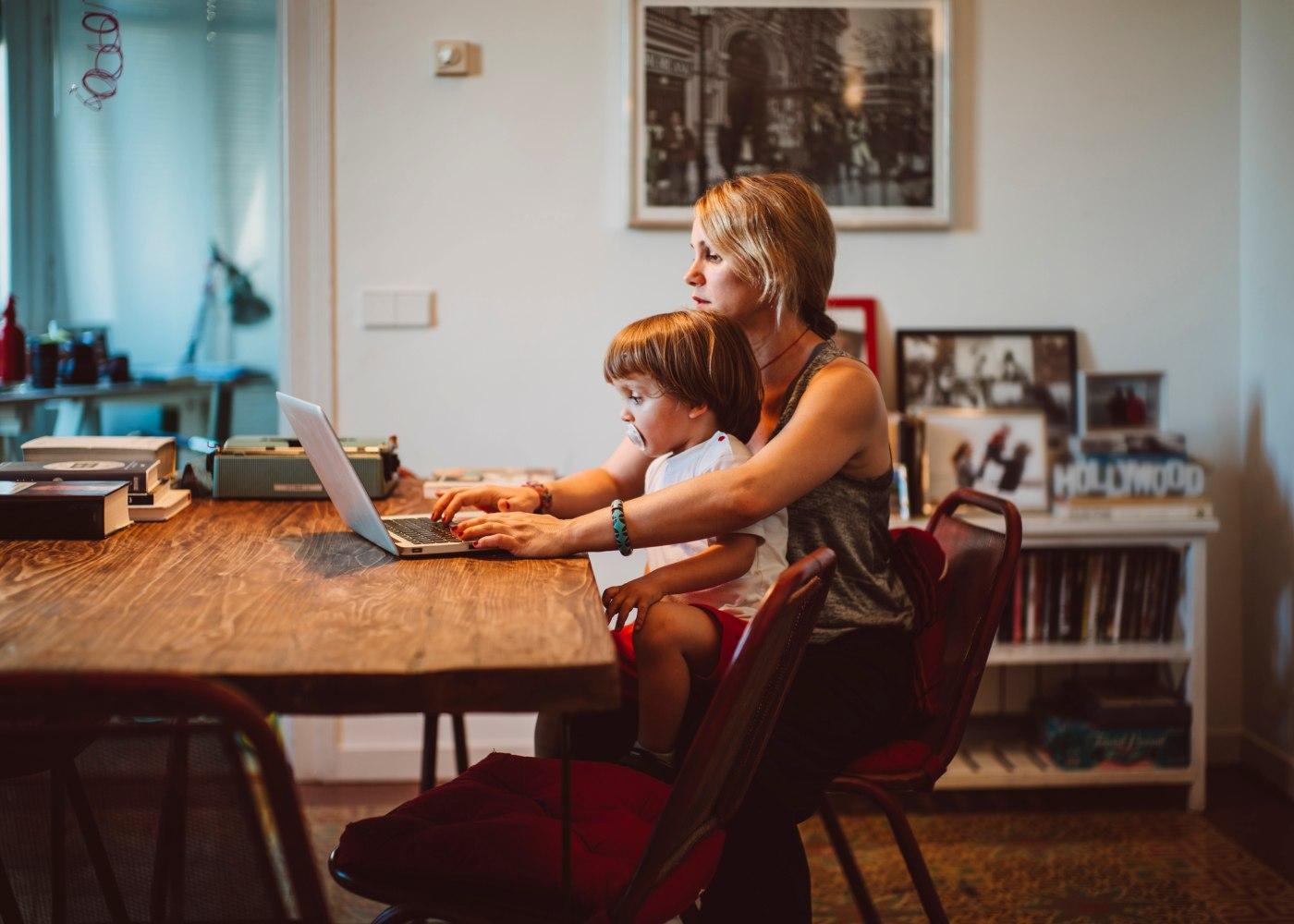 mãe a trabalhar ao computador com um filho ao colo