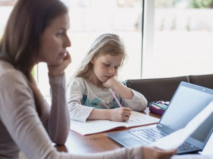 mãe a trabalhar em casa com filha a estudar ao lado