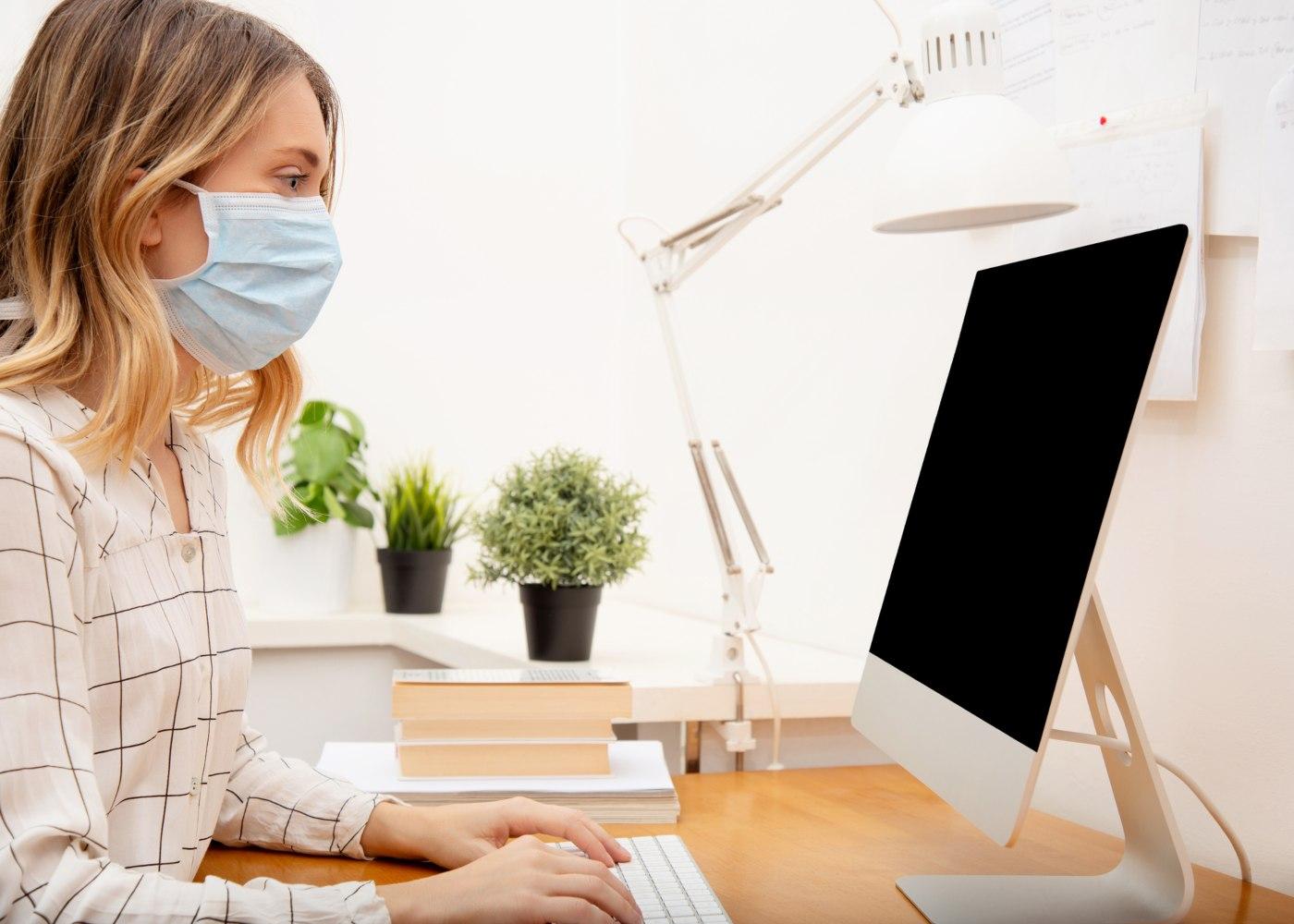 trabalho pós-pandemia no escritório mulher com máscara