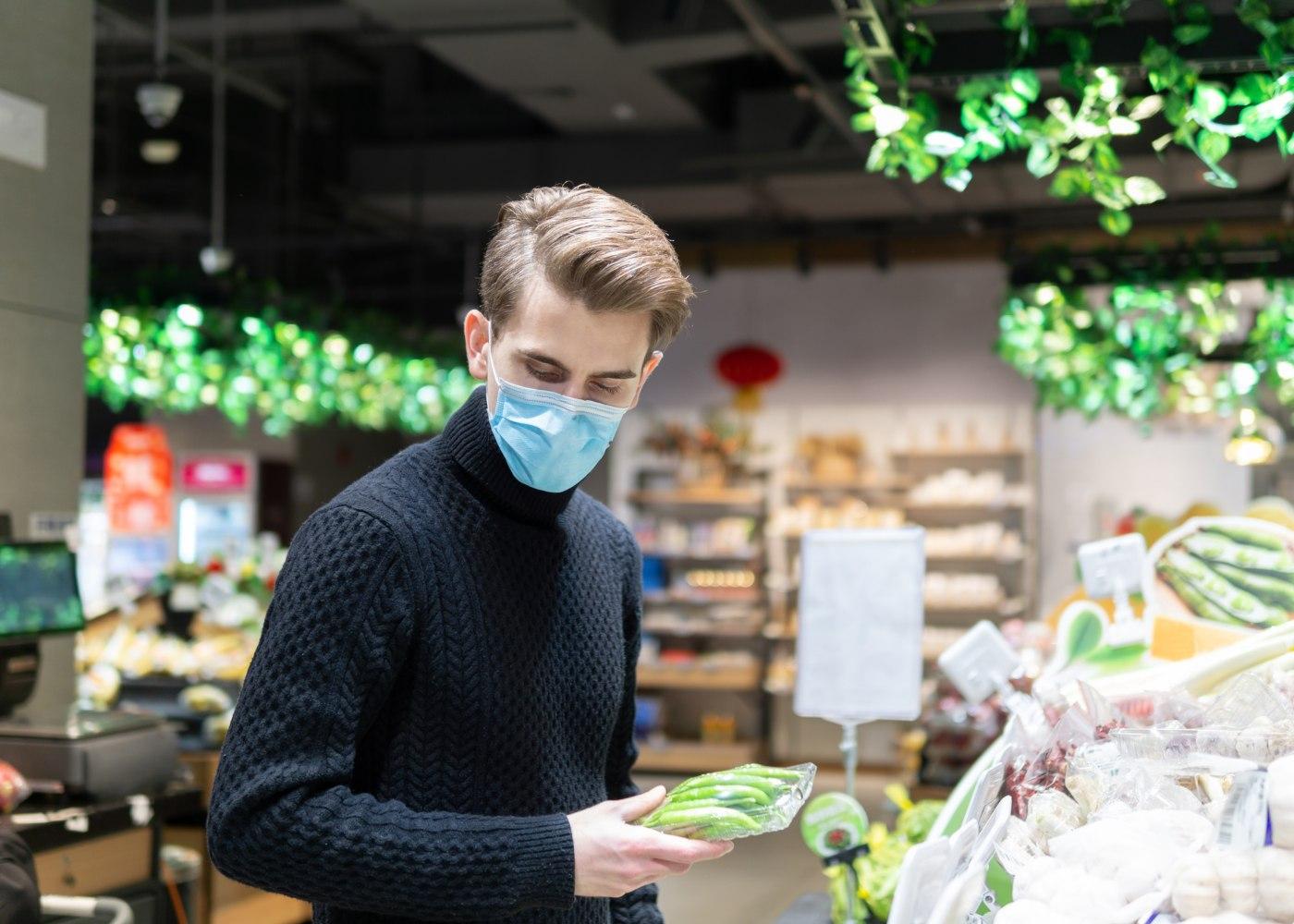 rapaz a fazer compras num supermercado como trabalho voluntário durante a pandemia