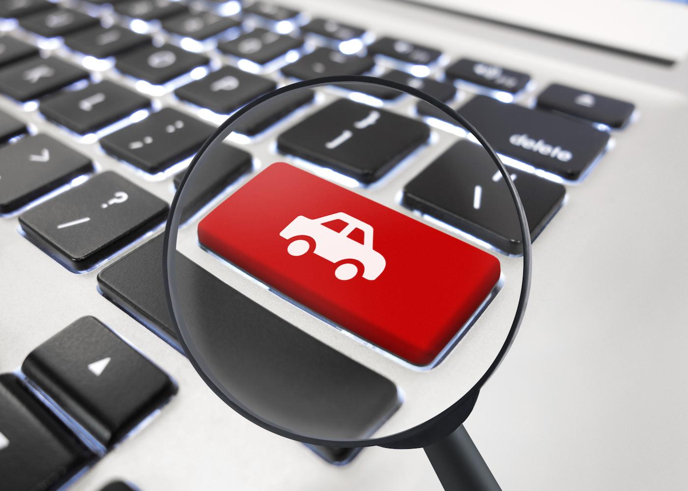 teclado de um computadpr com um carro desenhado no botão enter e uma lupa