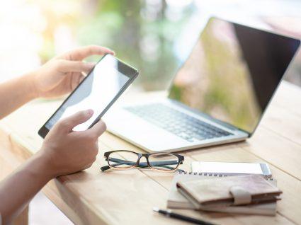 mãos de mulher a segurar um tablet com um computador sobre a mesa, óculos e carteira