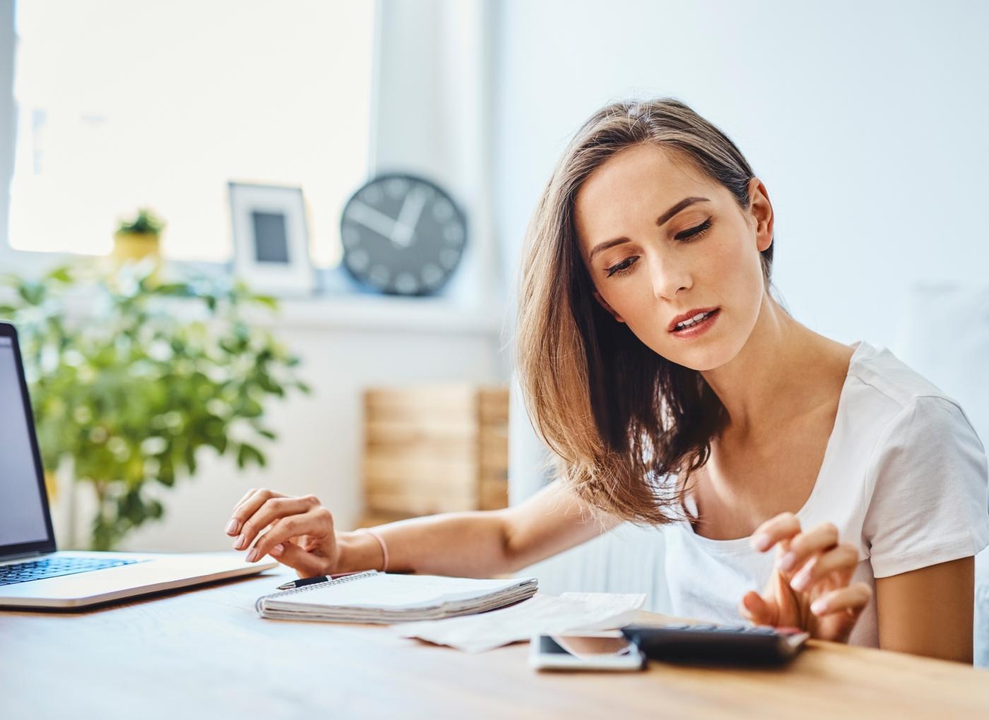 Mulher a fazer contas numa calculadora enquanto preenche declaração de IRS