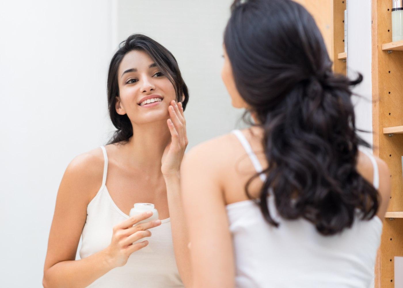 Mulher ao espelho a pôr esfoliante