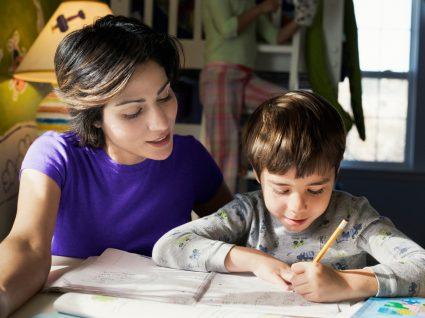 mãe a seguir indicações do guia para os pais e a ajudar o filho a estudar