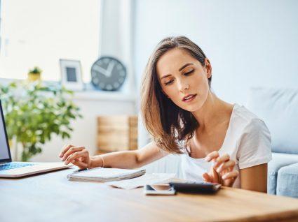 mulher a fazer o cálculo do seu salário tendo em conta as repercussões do layoff para o trabalhador