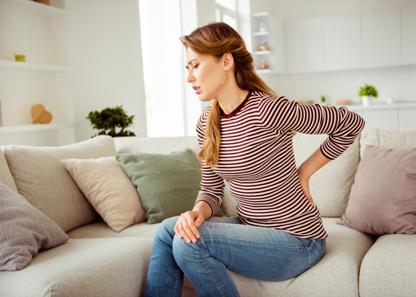 Jovem no sofá com lombalgia