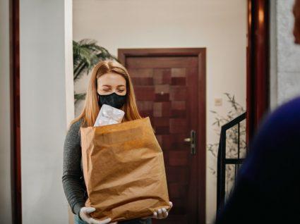 rapariga a entregar compras a pessoas de grupo de risco
