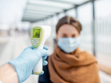 pessoa a medir a temperatura a funcionária na chegada ao trabalho