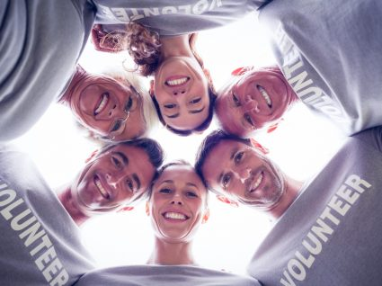 vista de baixo para seis pessoas voluntárias abraçadas