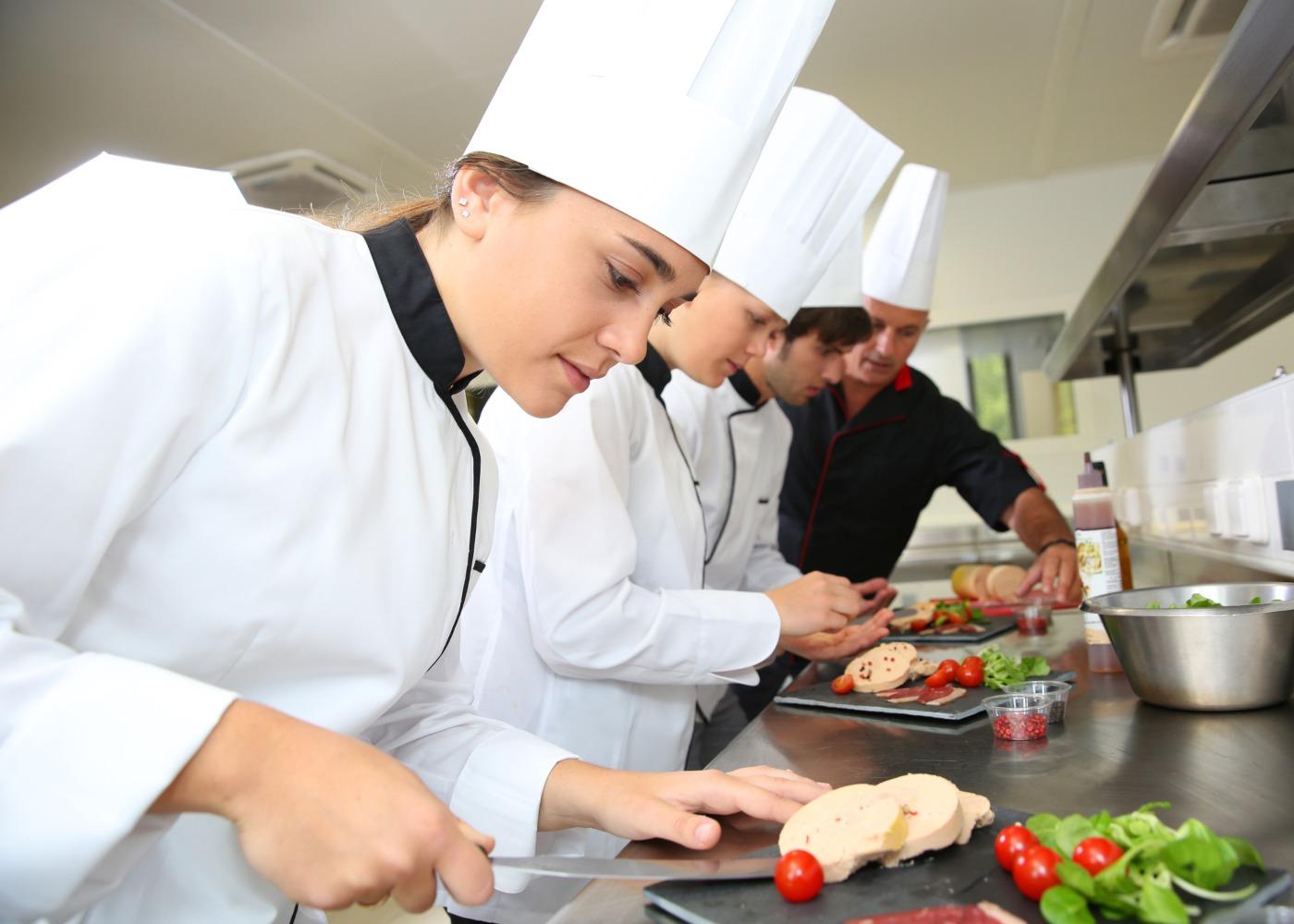estagiários de cozinha a preparar prato com o orientador