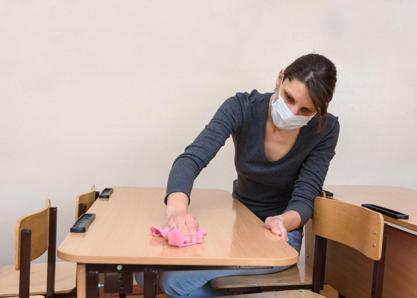 mulher a limpar as secretárias para cumprir normas de como vão funcionar as aulas presenciais