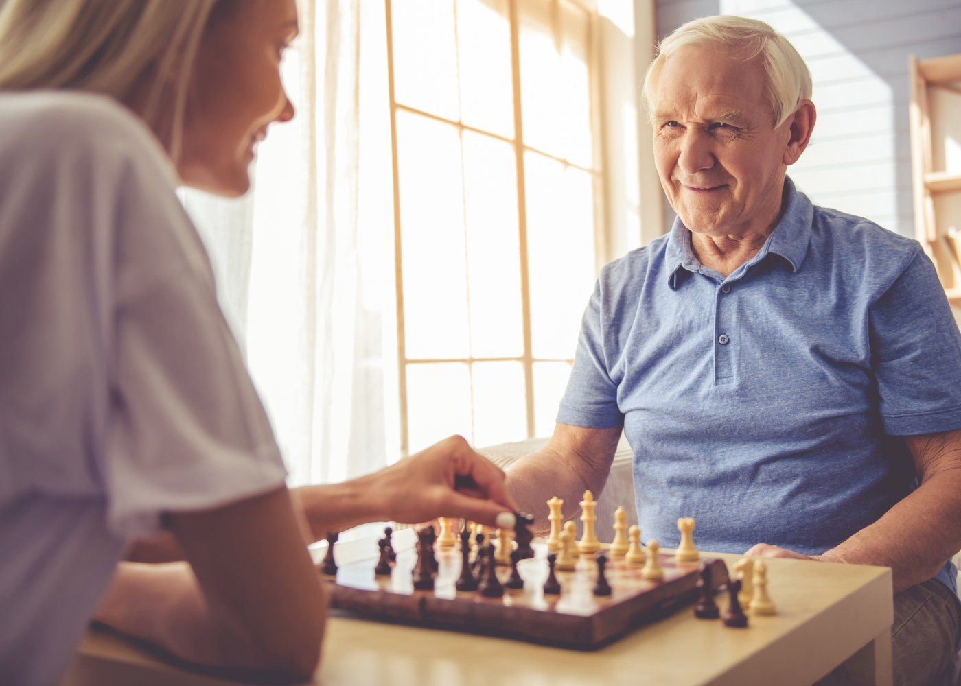 cuidadora a jogar xadrez com idoso