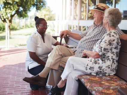 cuidador informal em tempos de pandemia a conversar com casal de idosos