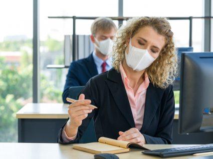 pessoas a cumprir os cuidados no regresso ao trabalho no escritório