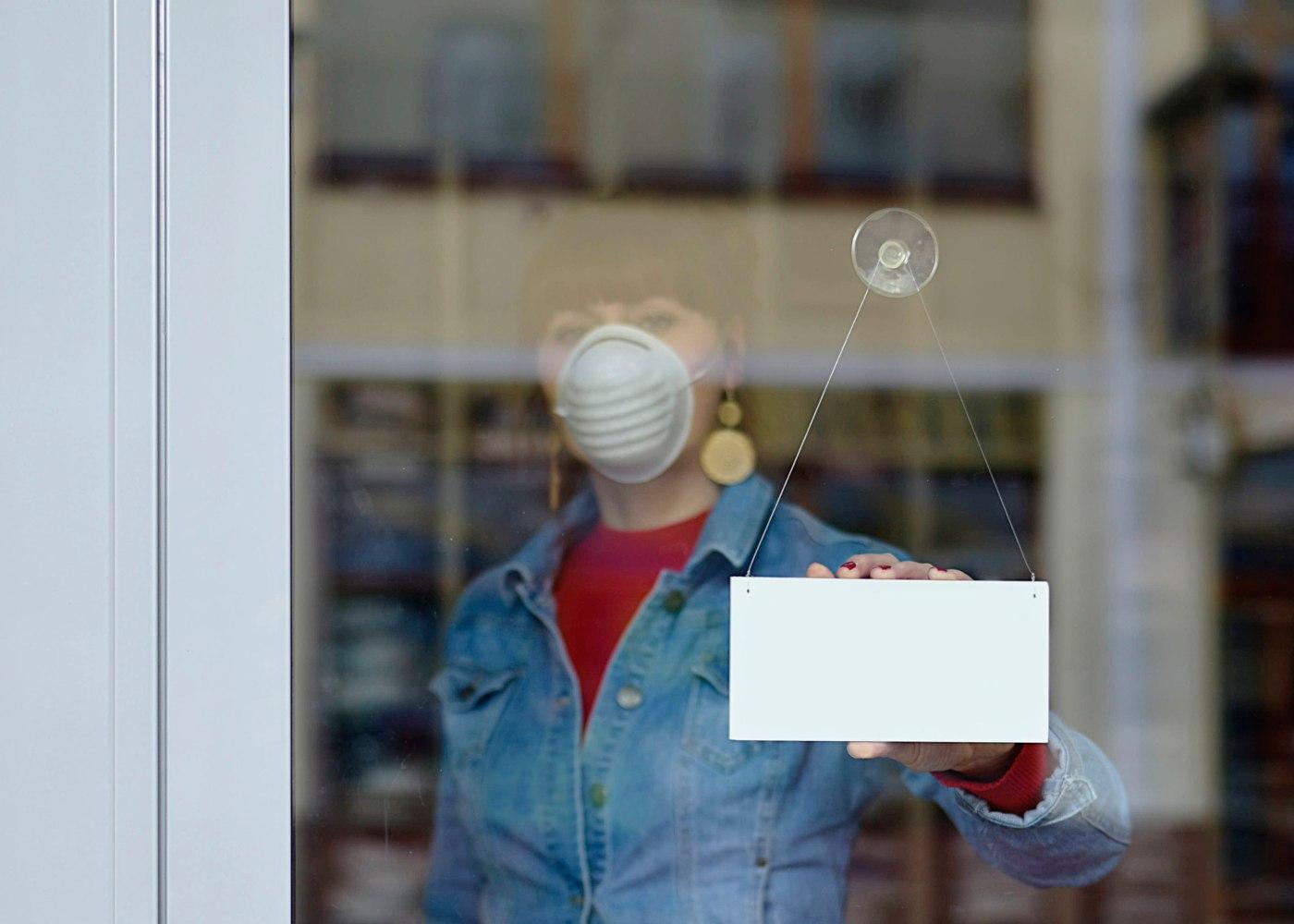 mulher com máscara a abrir loja