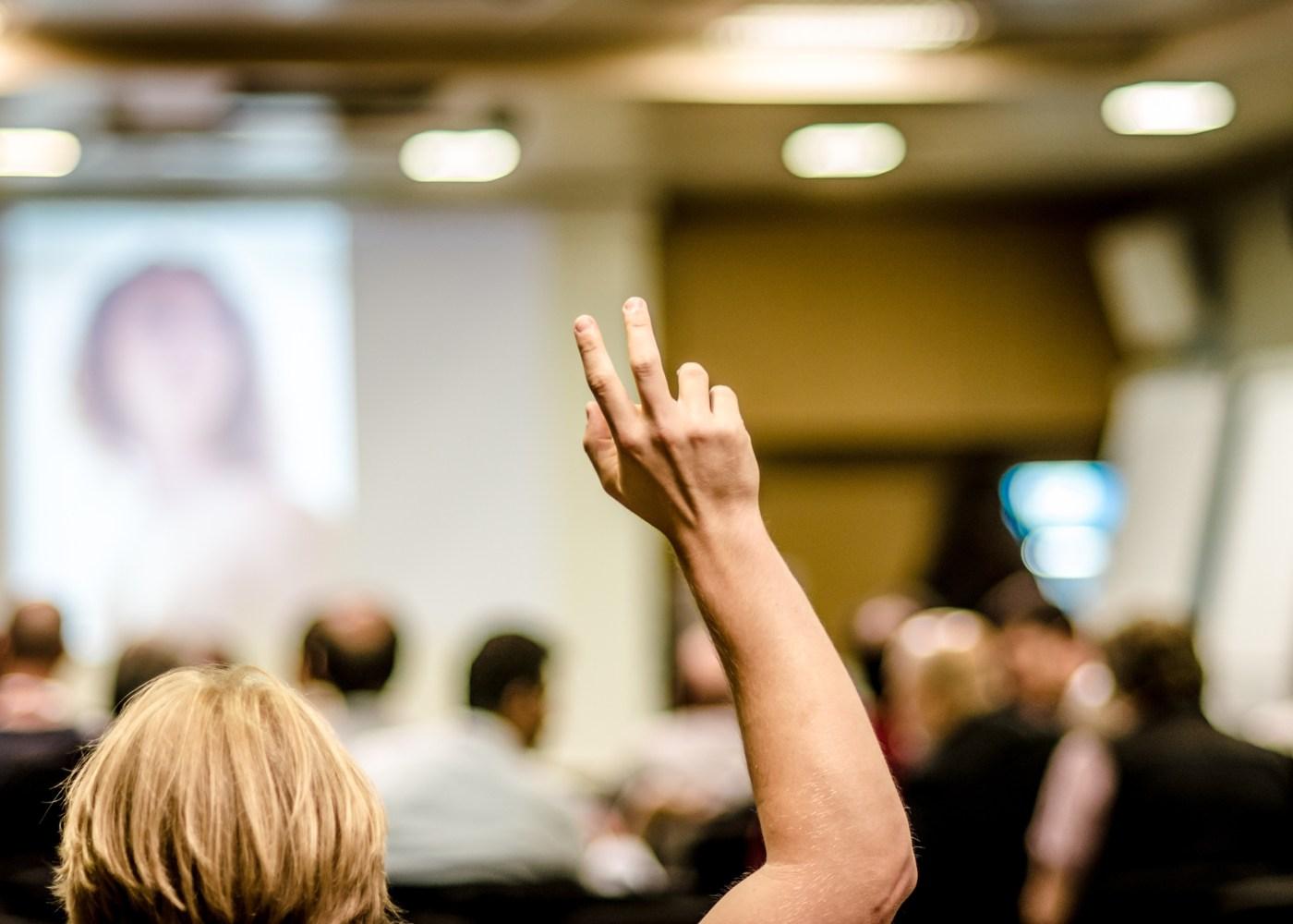 aluno com mão no ar numa aula
