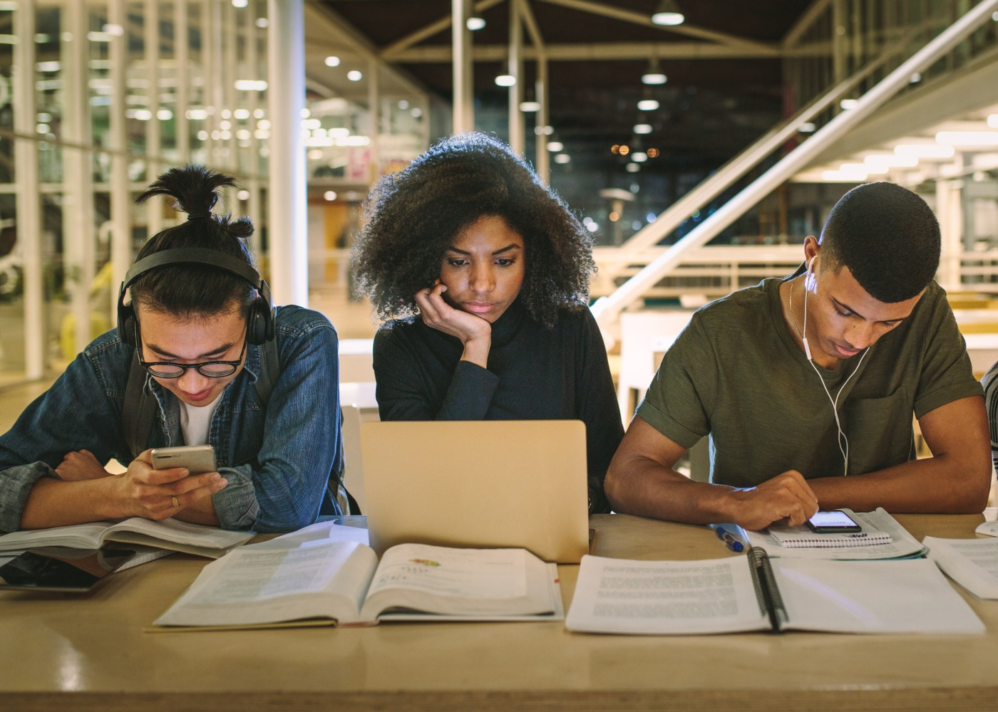 três jovens a estudar com cadernos e computadores