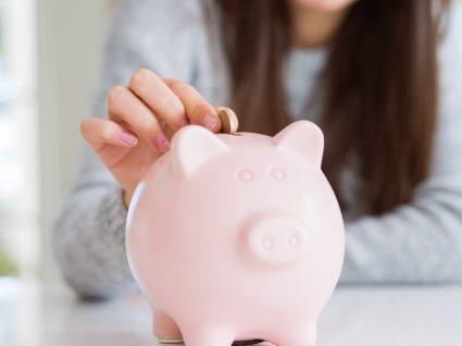 mulher a pôr uma moeda no mealheiro como parte do seu sistema de recompensa de poupanças