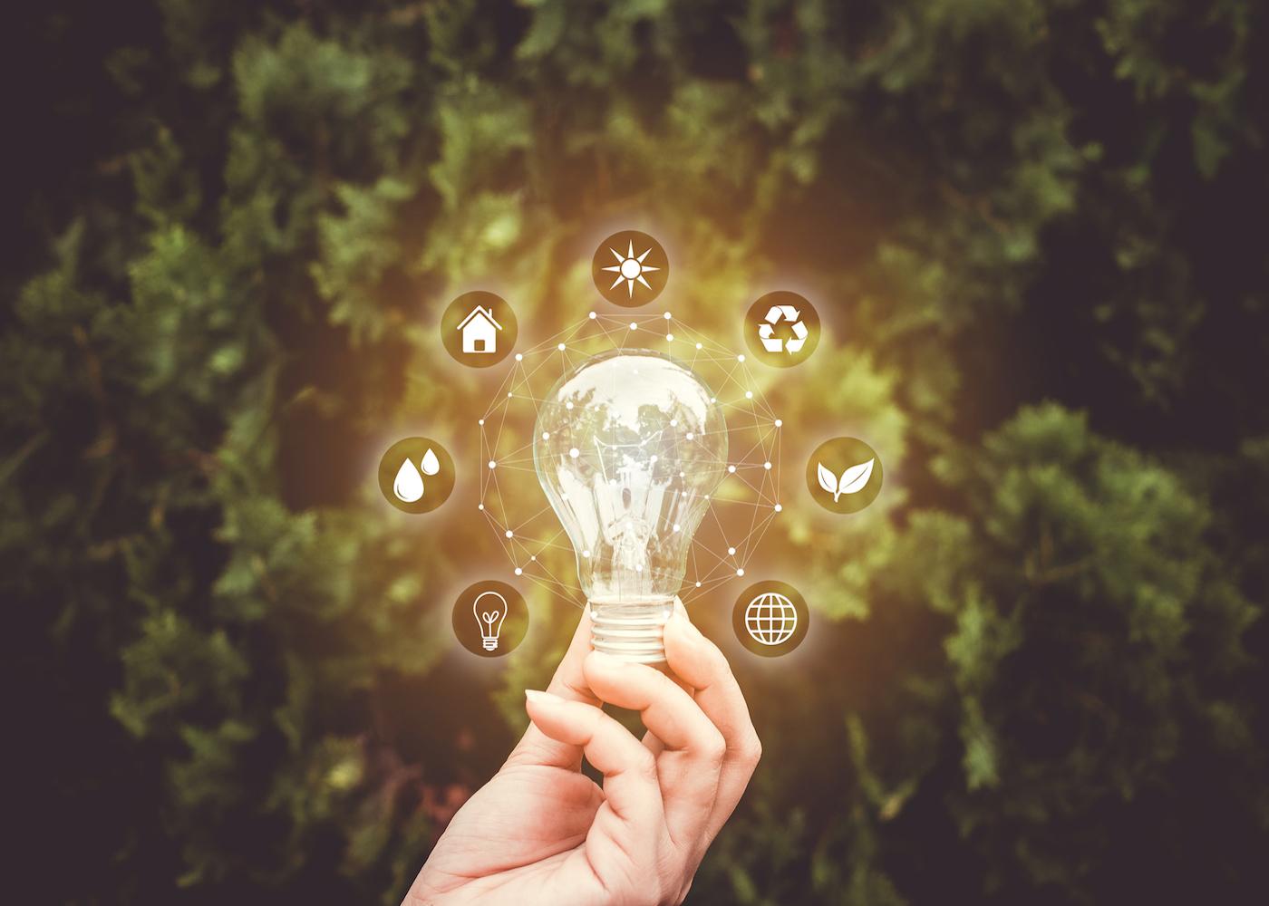 uma mão a segurar uma lâmpada com ícones de energia sustentável à volta