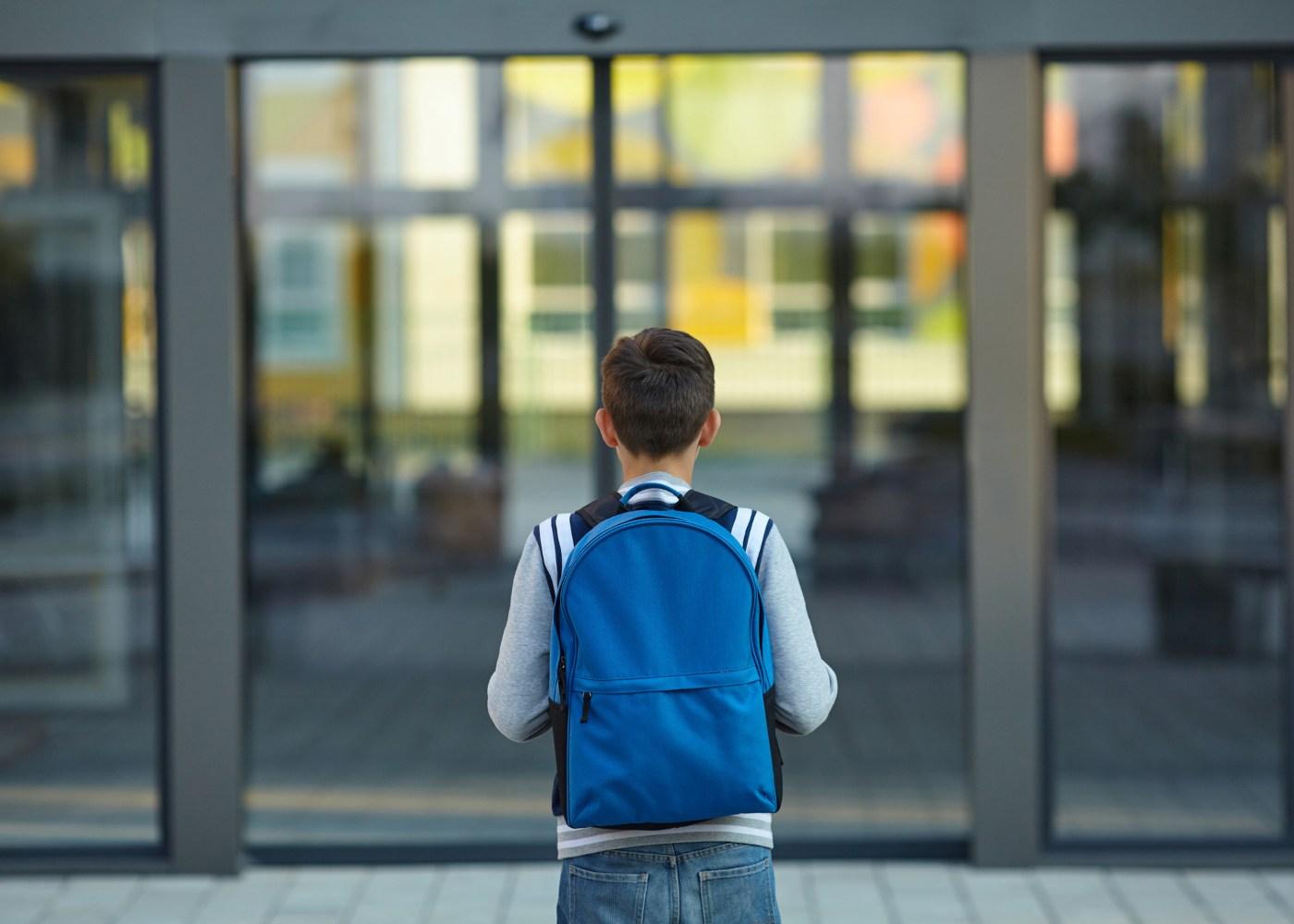 aluno parado à porta da escola