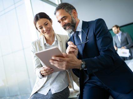 dois colegas a ver um tablet com ar feliz e motivado