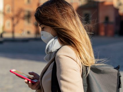 Mulher na rua com máscara de proteção
