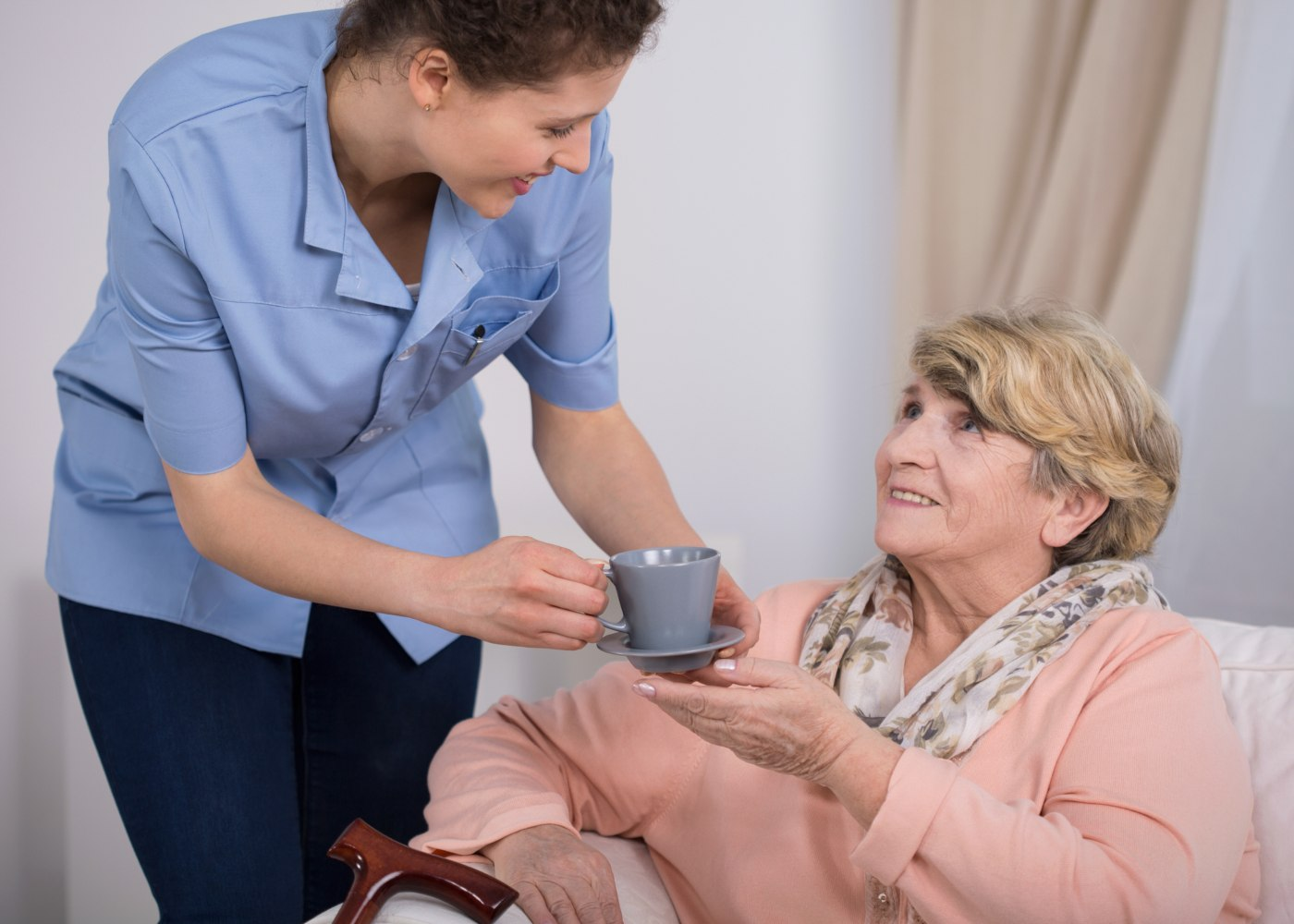 funcionária de lar a dar chá a uma idosa