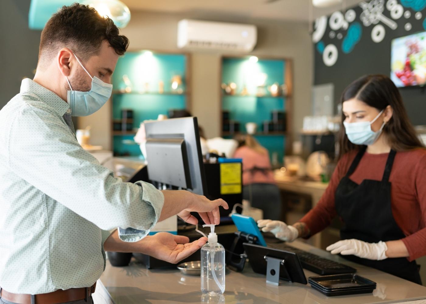 Homem a desinfetar as mãos depois de fazer pagamento em restaurante