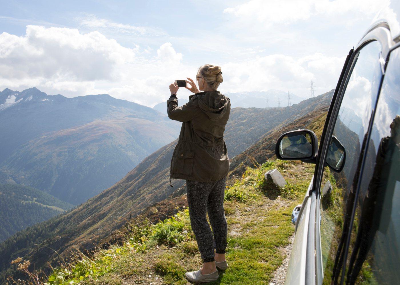 Mulher com smartphone a fotografar paisagem