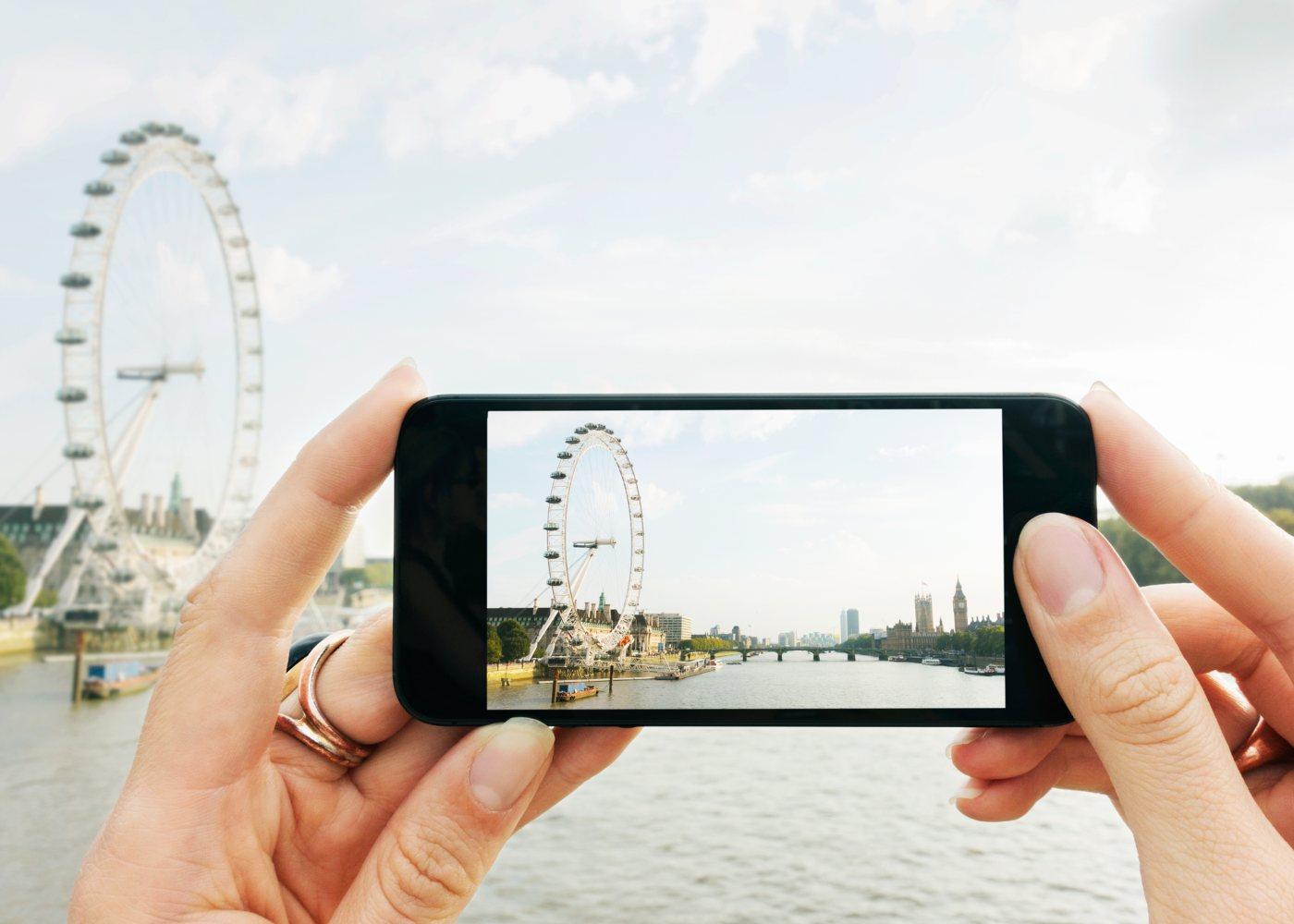 Mulher com smartphone a fotografar o London Eye