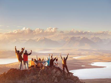 equipa feliz no topo de uma montanha