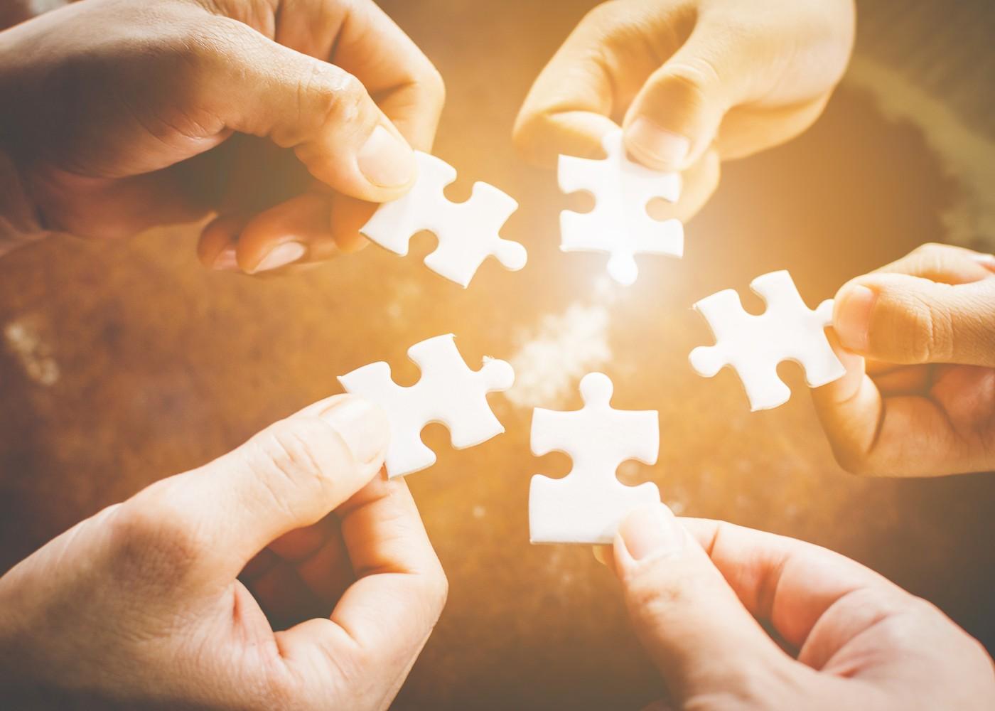mãos a segurar várias peças de um puzzle