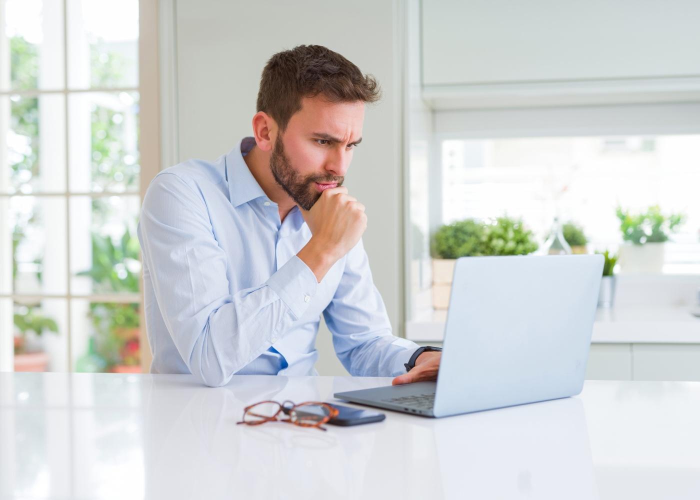 trabalhador ao computador com ar de preocupação