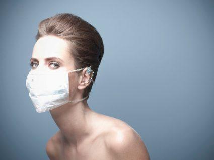Mulher a usar maquilhagem com a máscara