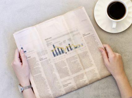Mulher lê notícia sobre a subida do PIB no jornal