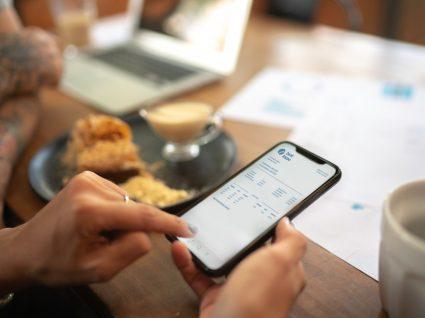 mulher tenta descodificar as siglas bancárias do seu extrato no telemóvel