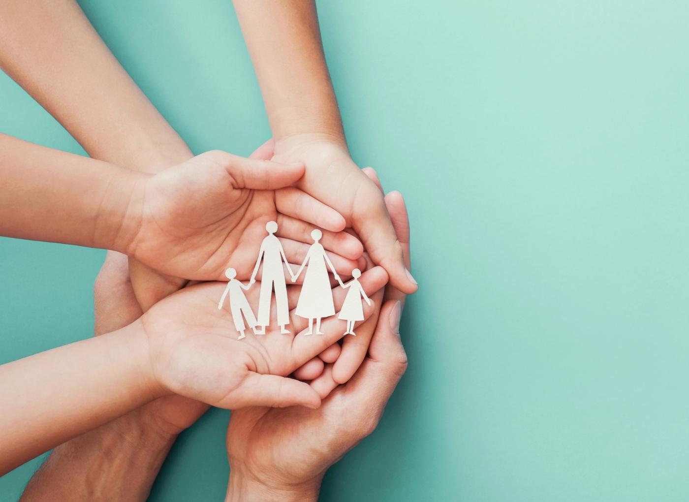 Mãos de adultos e crianças a segurar um recorte em papel de uma família