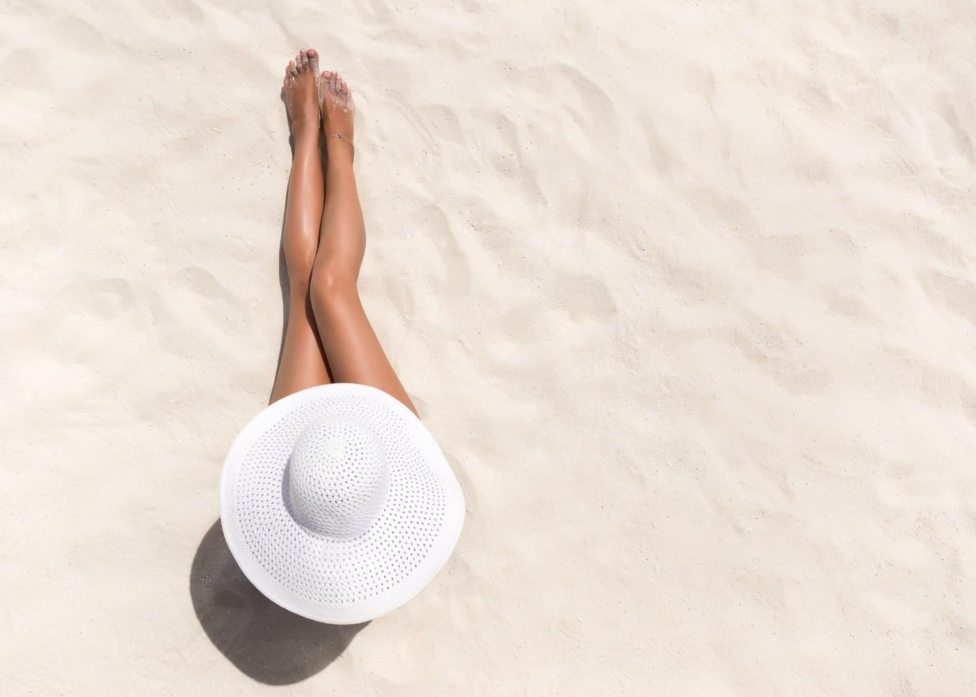 Mulher na praia com pernas bronzeadas