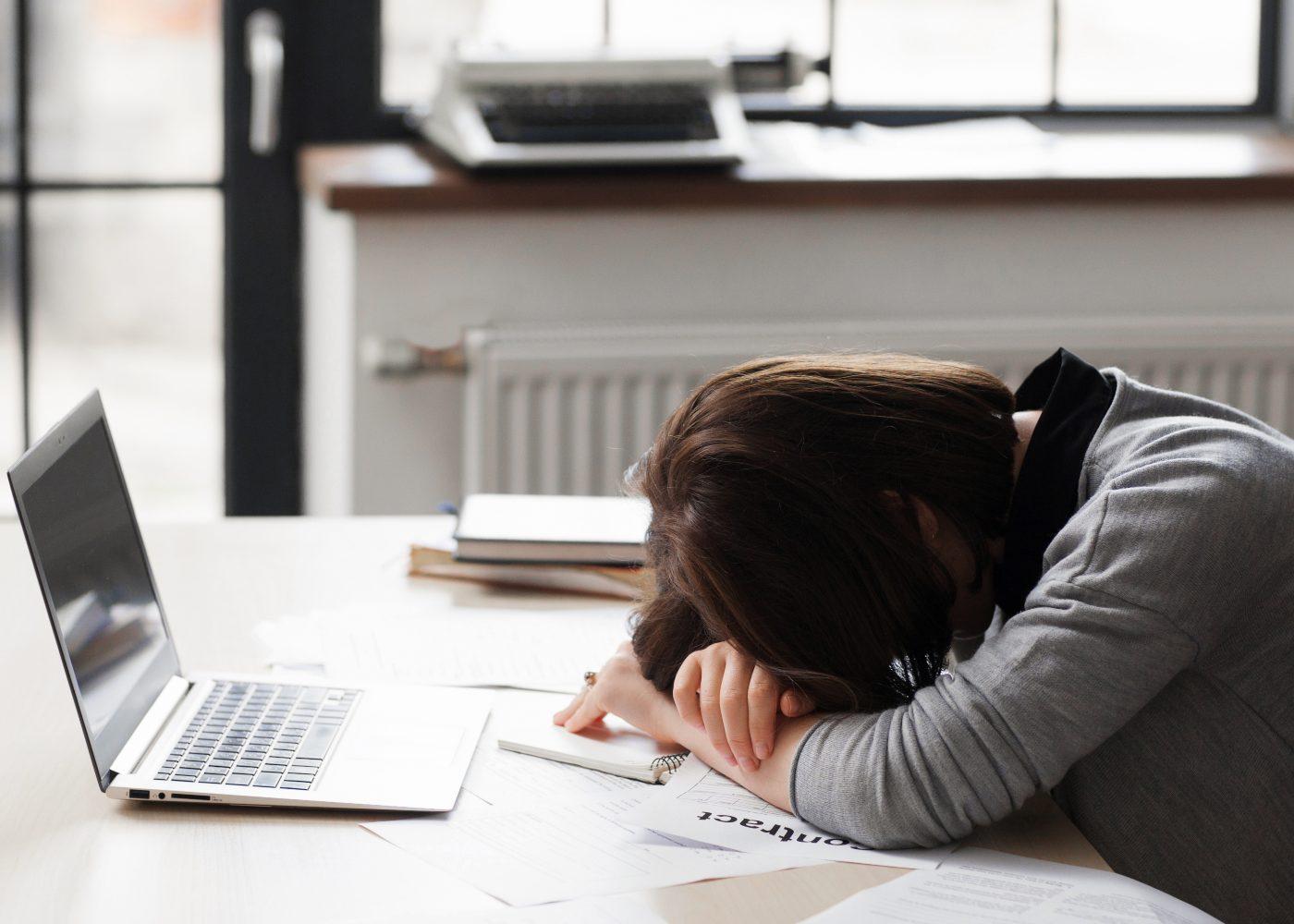 mulher exausta deitada a frente do computador em situação de precariedade
