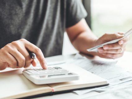 Homem a fazer contas às vantagens de pedir moratória de crédito