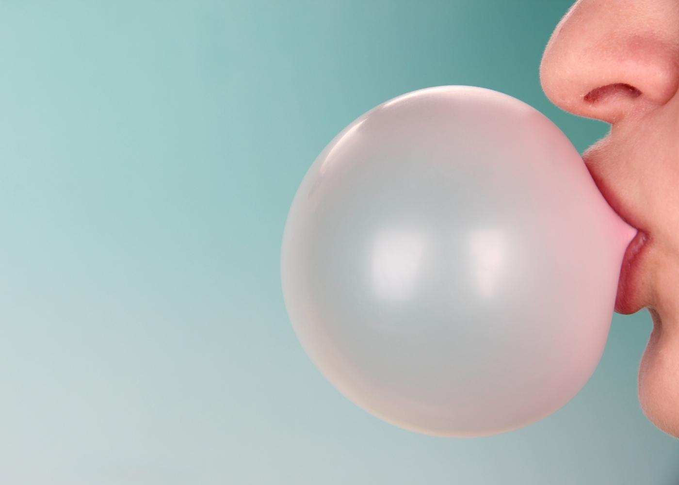 Mulher a fazer uma bola de pastilha elástica