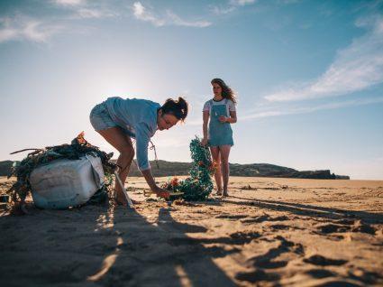 economia circular: duas mulheres recolhem lixo na praia para utilizar como matéria prima