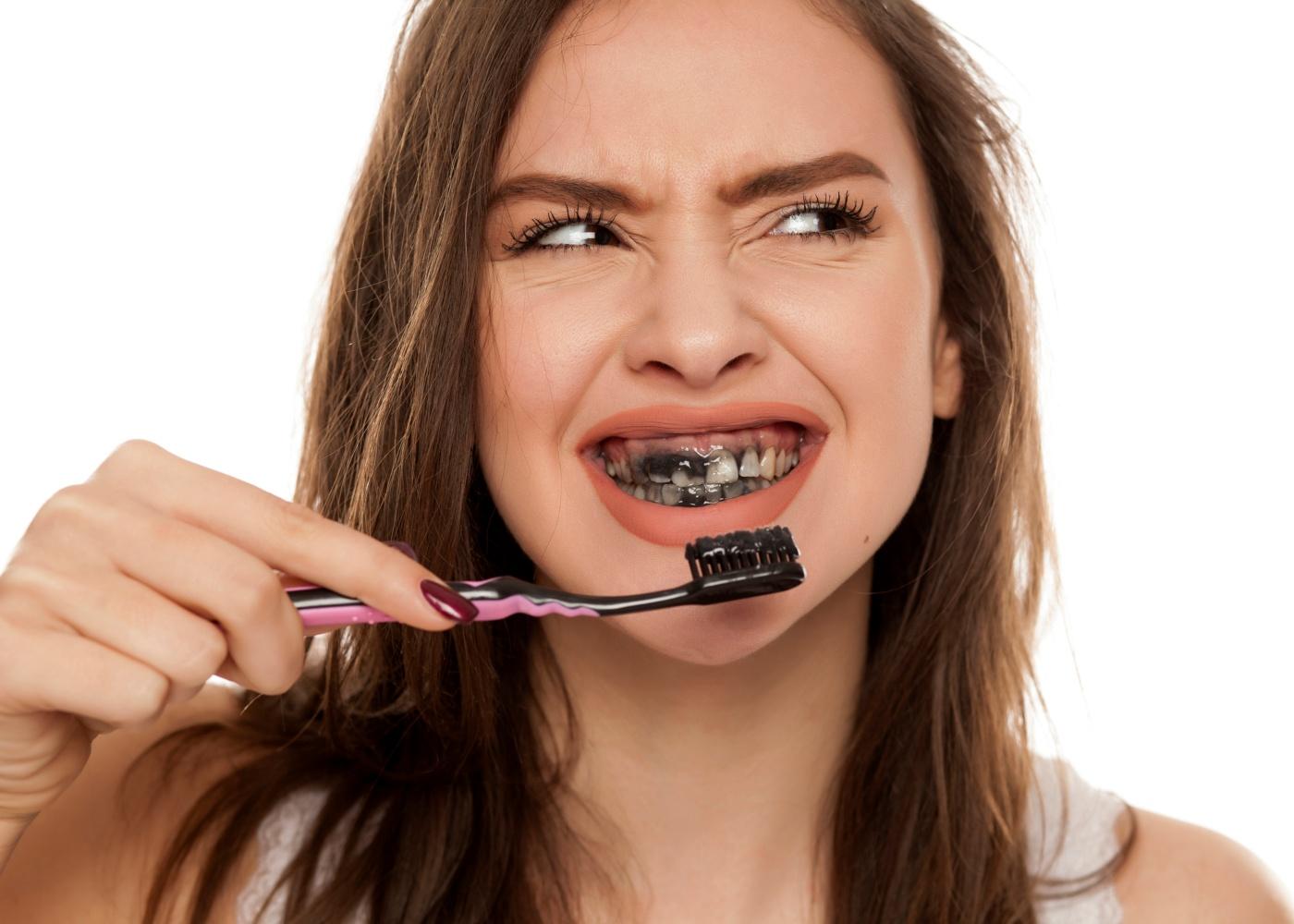 Mulher a lavar os dentes com pasta dos dentes preta